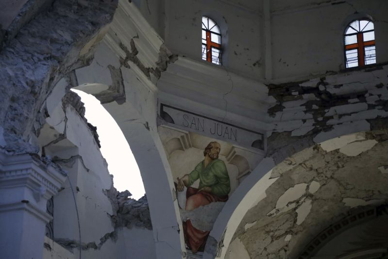 CORRECTS AGE OF BABY TO TWO MONTHS, NOT TWO YEARS - The Santiago Apostol church stands damaged after the 7.1 earthquake in the town of Atzala in Puebla state, Mexico, Wednesday Sept. 20, 2017. According to family related to 11 relatives who died inside the church during Tuesday's quake, the roof collapsed during a Mass held to baptize a two-month-old girl, and the only people who survived were the baby's father, the priest and the priest's assistant. (AP Photo/Pablo Spencer)