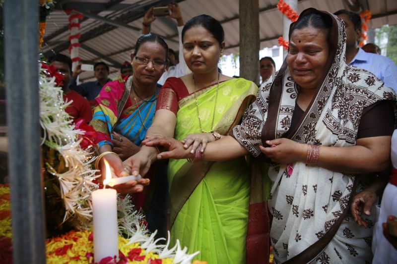 Shushila Ughade, right, who lost her husband in Mumbai terror attacks, light the candle along with others at the memorial on the ninth anniversary in Mumbai, India, Sunday, Nov. 26, 2017. The attack by Pakistani gunmen in India's financial capital on Nov. 26, 2008 killed 166 people and shattered relations between the nuclear-armed neighbors. (AP Photo/Rafiq Maqbool)