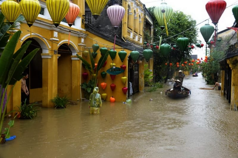 Local residents use a boat as others wade in the flooded tourist town of Hoi An (AFP Photo/STR)