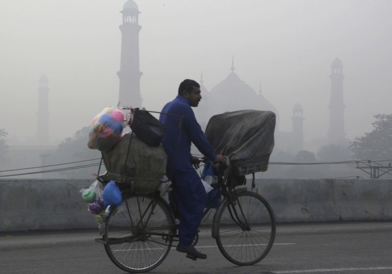 A cyclist passes by the historical Badshahi Mosque while smog envelopes the area in Lahore, Pakistan, Sunday, Nov. 5, 2017. Smog has enveloped much of Pakistan and neighboring India, causing highway accidents and respiratory problems, and forcing many residents to stay home, officials said. (AP Photo/K.M. Chaudary)