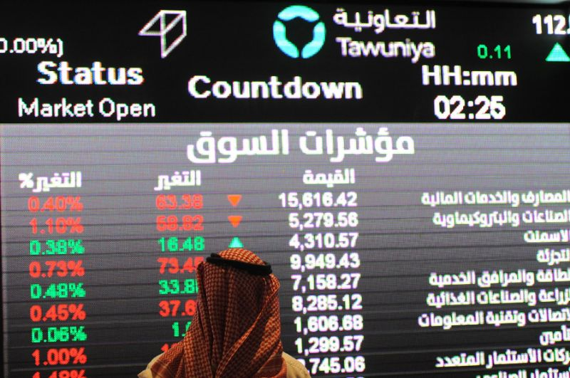 This file photo taken on December 14, 2016 shows a Saudi investor inspecting the stock exchange monitors at the Saudi Stock Exchange, or Tadawul, in the capital Riyadh