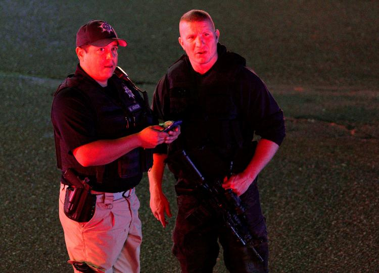 Police compare an image on a smartphone to a person they spotted in the crowd at the scene of a shooting at a Walmart in Thornton, Colo., the night of November 1.