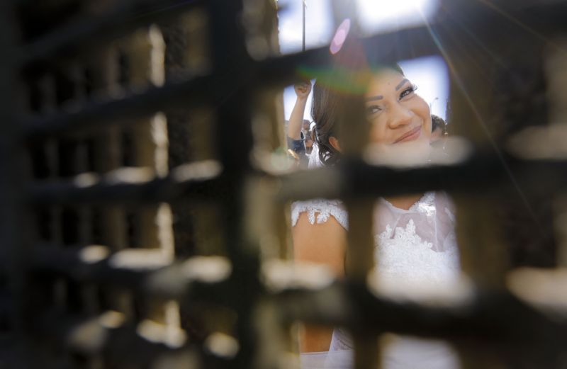 In this Nov. 18, 2017, photo, Evelia Reyes looks into the United States at Friendship Park, part of Border Field State Park, through the border fence from the Mexico side, before getting married to Brian Houston at the