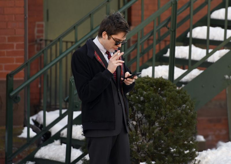 Lucian Wintrich, White House correspondent for the right-wing blog Gateway Pundit, smokes a cigarette while looking at his phone near Rockville Superior Court in Vernon, Conn., Monday, Dec. 11, 2017. Charges of breach of peace against Wintrich were dropped stemming from a Nov 28 incident at the University of Connecticut at which Wintrich delivered a speech titled