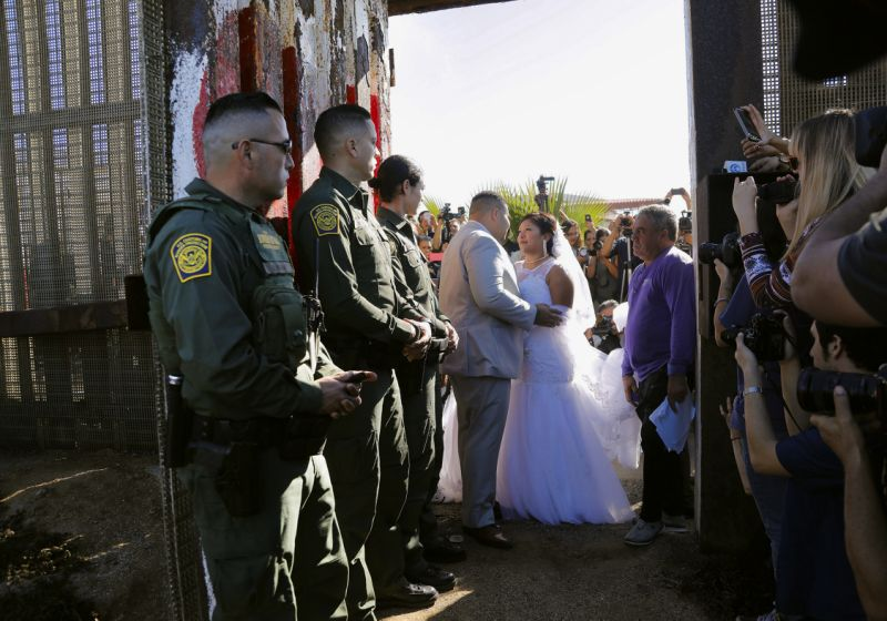 In this Nov. 18, 2017, photo, Brian Houston, of Rancho San Diego, center left, and Evelia Reyes, right, of Tijuana, Mexico, look at each other in their wedding at the