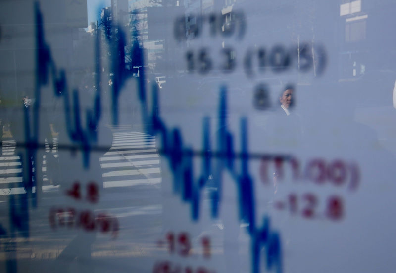 © Reuters. A man is reflected on an electronic board showing a graph analyzing recent change of Nikkei stock index outside a brokerage in Tokyo