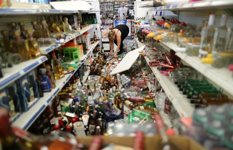 An employee cleans up toppled bottles in a convenience store on July 6, 2019 following a 7.1-magnitude earthquake in Ridgecrest, California (AFP Photo/MARIO TAMA)