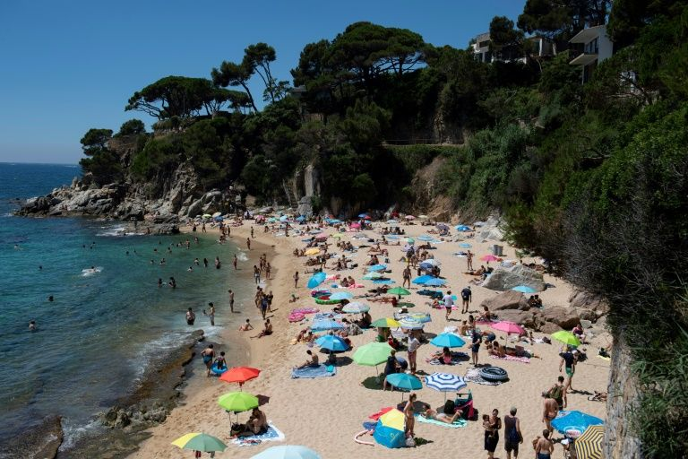 People enjoy a day out at the beach in Platja D'Aro near Girona -- Spaniards endured one of the world's toughest lockdowns for three months from March 2020 (AFP Photo/Josep LAGO)
